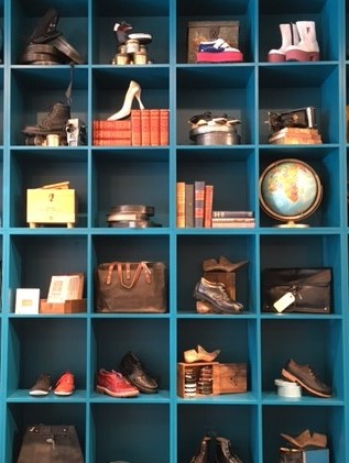dark blue bookshelf artistically displayed books, shoes, globes, and bags