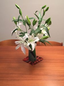 white bouqet of lilies in a vase on wooded table