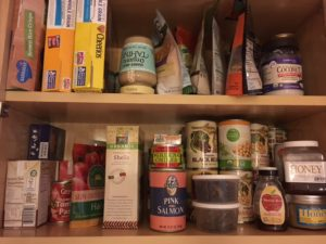 food pantry with cereals on left side of top shelf and bags of grains lined up. Second shelf, below are canned foods, box of pasta, containers of dried mushrooms and jars of honey