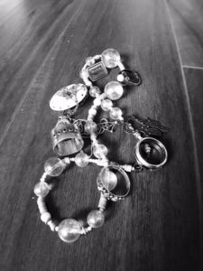 black and white image of piled on jewelry such as necklaces, rings and pins.