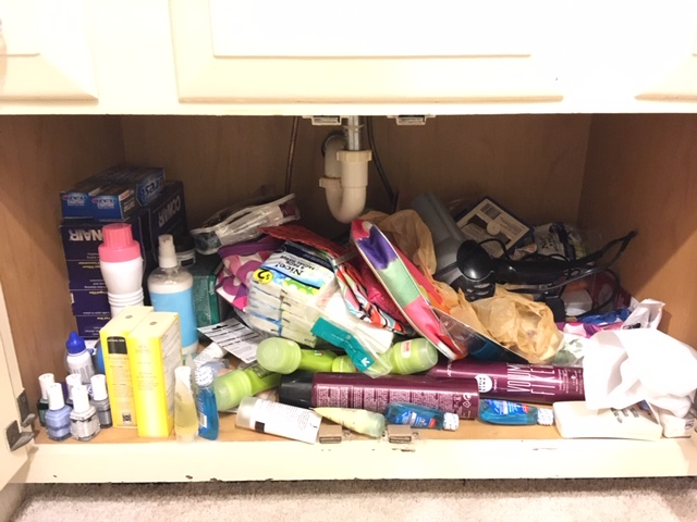 Chaos in cabinent full of hair products and oral products